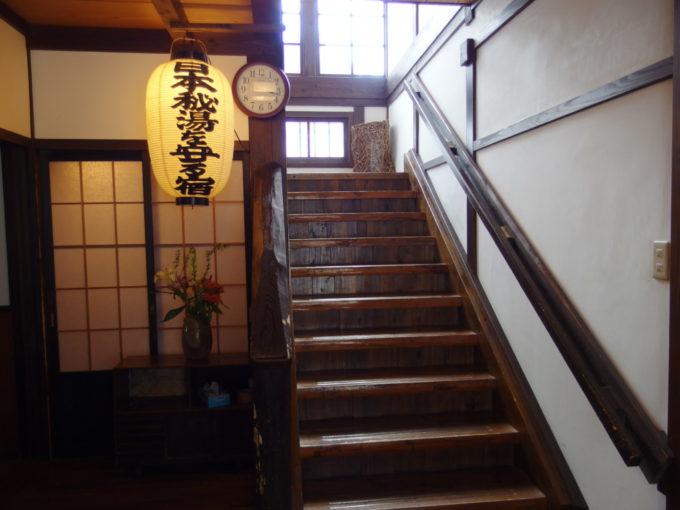 冬の乳頭温泉郷鶴の湯3号館玄関からのびる渋い木の階段と日本秘湯を守る会の提灯