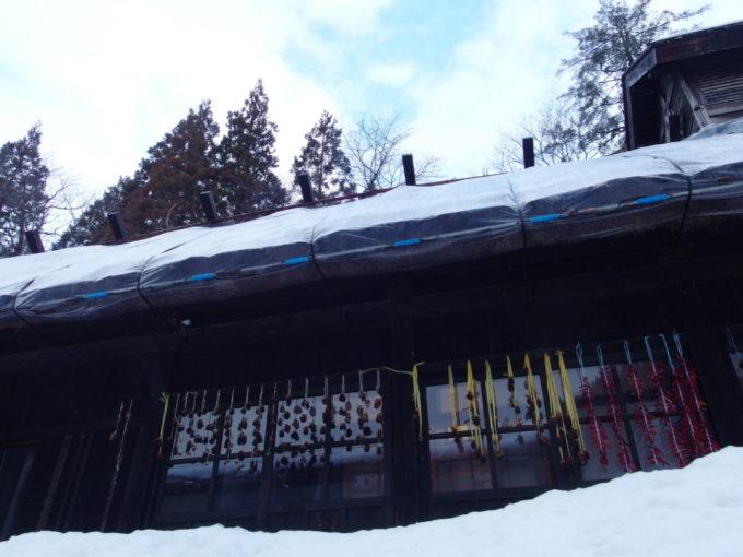 冬の乳頭温泉郷鶴の湯本陣の軒下に吊るされた柿や鷹の爪