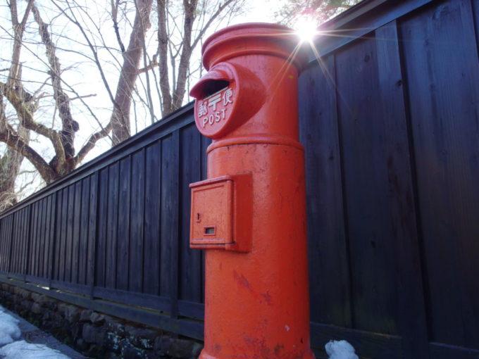 冬の角館冬晴れの太陽と黒塀に映える赤い古いポスト