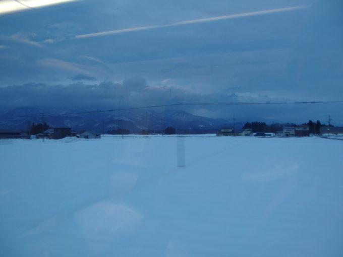 秋田新幹線E6系こまち号車窓を染める夕闇の雪原