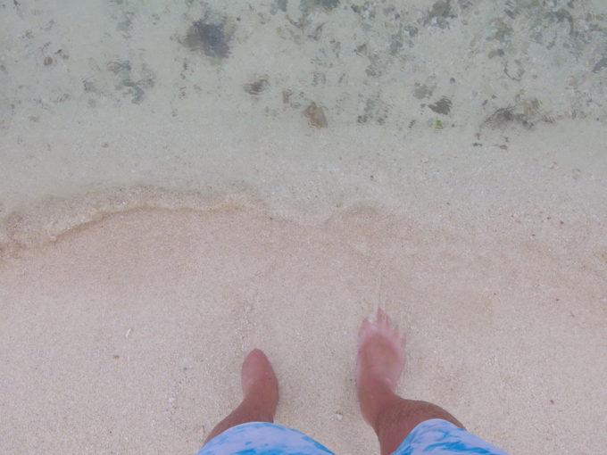夏の竹富島曇天のコンドイビーチで波と戯れる
