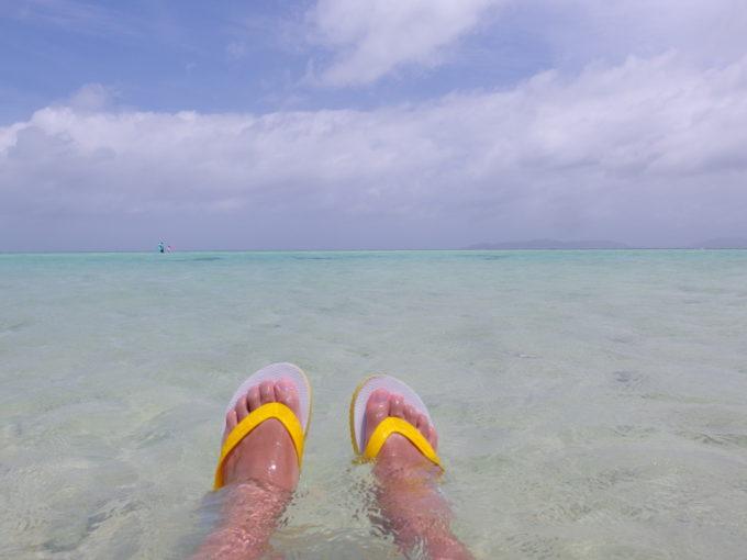 夏の石垣島竹富島コンドイビーチ波打ち際に座り海と戯れる