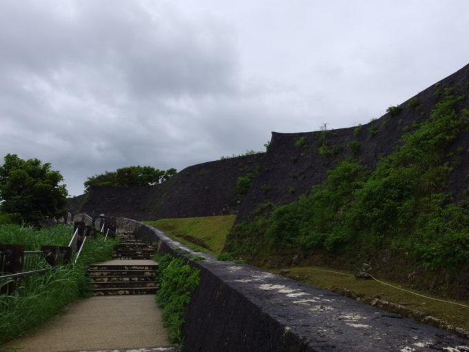 夏の沖縄那覇首里城雨上がりの黒い石垣沿いに歩く道