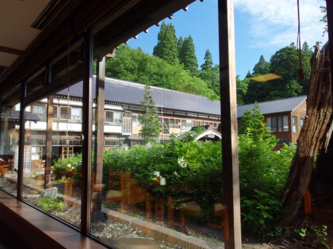 夏の蔦温泉旅館レストランの大きな窓から眺める朝日に照らされた大正時代築の本館