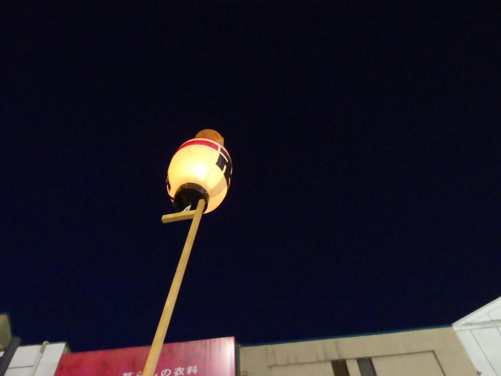 夏の弘前ねぷた天を突く市役所の市章入り提灯