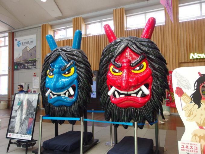 秋田駅コンコースで旅人を出迎えるなまはげの巨大なお面