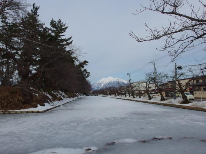 雪のない冬の弘前結氷した弘前城のお堀の先に聳える岩木山