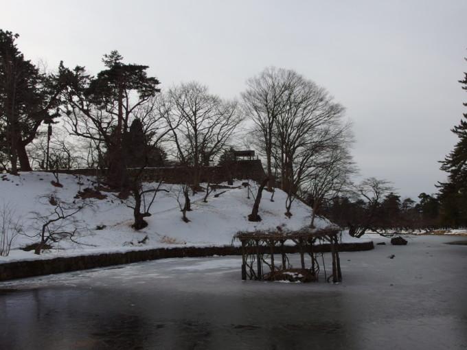 雪のない冬の弘前蓮池越しに眺める本丸戍亥櫓跡と雪化粧の石垣