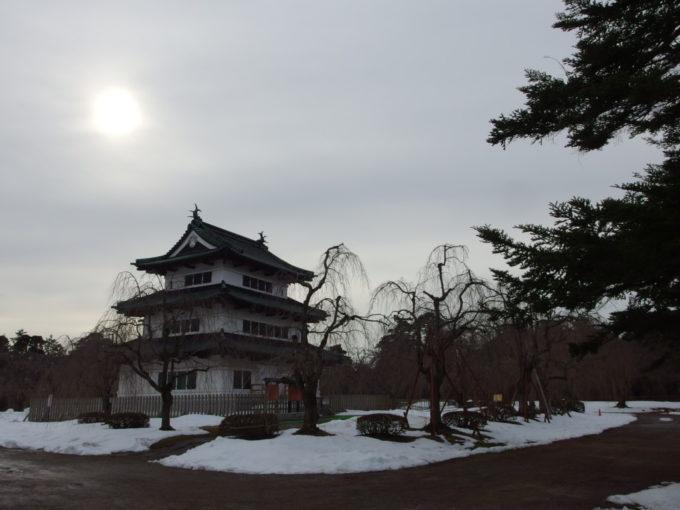 雪のない冬の弘前冬の弱い太陽を背負う弘前城天守閣