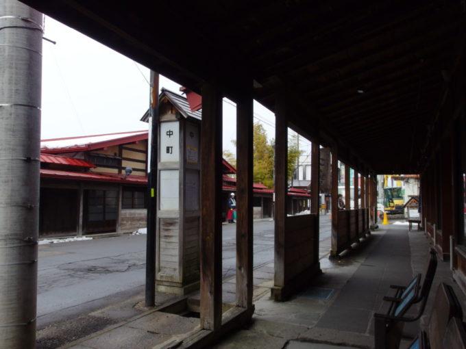 雪のない冬の黒石こみせ通り雨の中こみせの軒下でバスを待つ