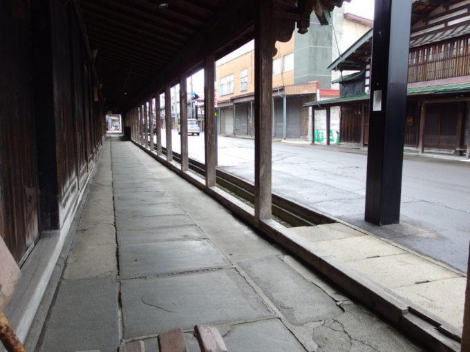 雪のない冬の黒石こみせ通り軒下でバスを待つひととき