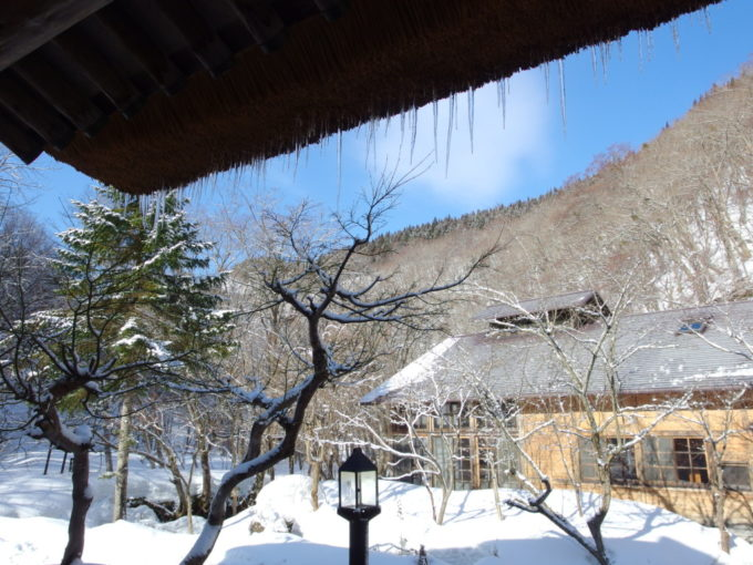 冬のランプの宿青荷温泉抜けるような青空と茅葺屋根に連なるつらら