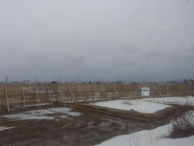 冬の奥羽本線を守る丸太と茅で作られた仮設の防雪柵