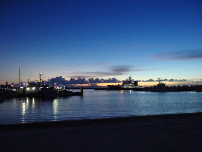 6月下旬人の少ない石垣島夕闇迫る港湾と海上保安庁巡視船のシルエット