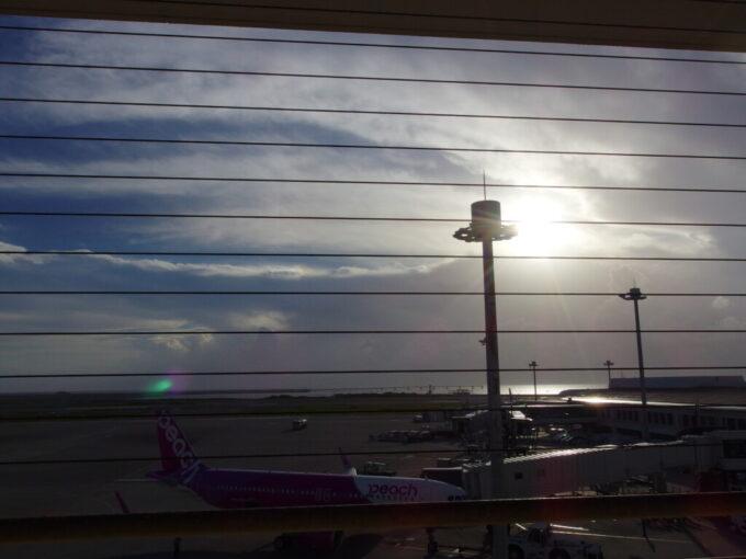 6月下旬人の少ない那覇空港西日に輝くターミナルと海
