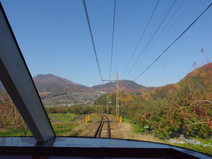 11月中旬長電ゆけむり号後展望の車窓に広がる秋晴れの空と赤いりんごの実