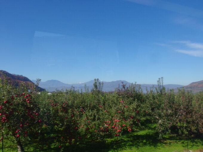 11月中旬長電ゆけむり号車窓から望む秋晴れの空と赤いりんご